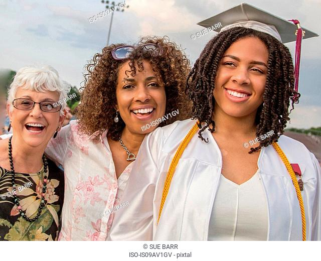 Teenage girl with mother and grandmother at graduation ceremony