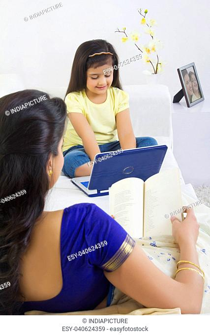 Mother reading a book while daughter plays with computer
