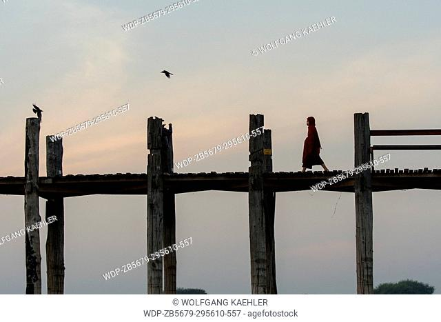 A monk is walking before sunrise on U Bein Bridge (built around 1850 and is believed to be the oldest and longest teakwood bridge in the world) in Mandalay