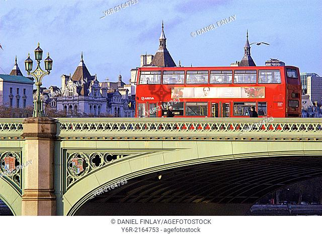 Red double-decker bus crossing Westminster Bridge in the heart of London, England