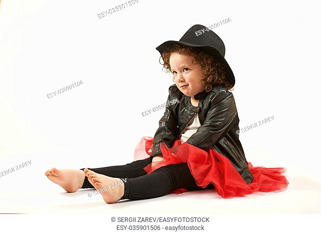 Little girl with black hat sitting and looking up