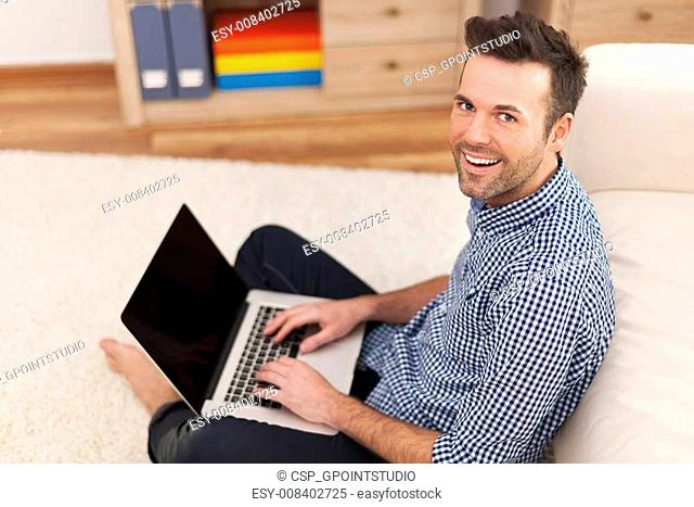 Smiling man sitting on floor with laptop