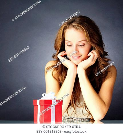 Portrait of a girl sitting and looking at a gift box