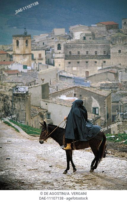 Man with cloak riding a mule, Palazzo Adriano, Sicily, Italy