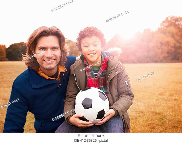 Portrait smiling father and son with soccer ball in park grass