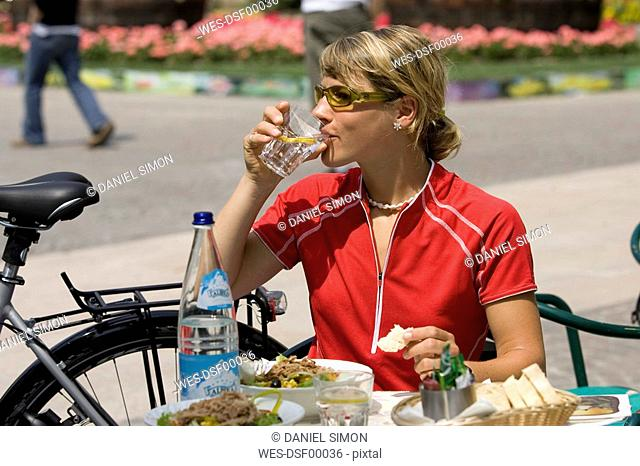 Italy, Trento, Arco, Woman with mountainbike drinking water