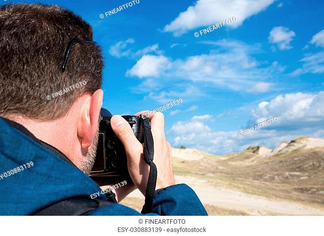 Rear view of a photographer taking pictures of sand and sky landscape on sunny day