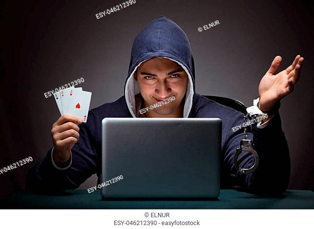 Young man in handcuffs wearing a hoodie sitting in front of a laptop computer gambling