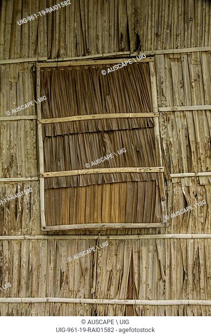 A house wall of palm fronds in framework with a removable panel in a window space. Pulau Gam island, Raja Ampat islands, Papua Province, Indonesia