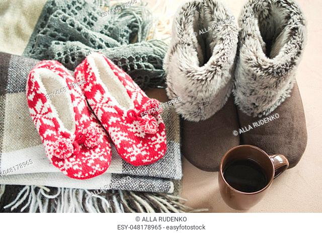 Warm home clothes. Woolen plaid and home slippers and cup of hot beverage