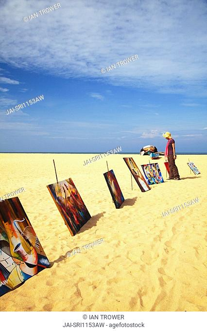 Woman looking at paintings on beach, Negombo, Sri Lanka MR
