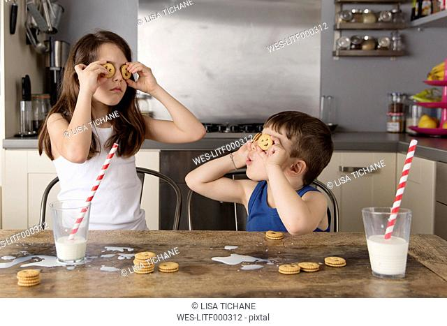 Little girl and boy covering their eyes with cookies
