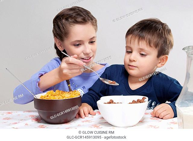 Girl feeding cereal to her brother