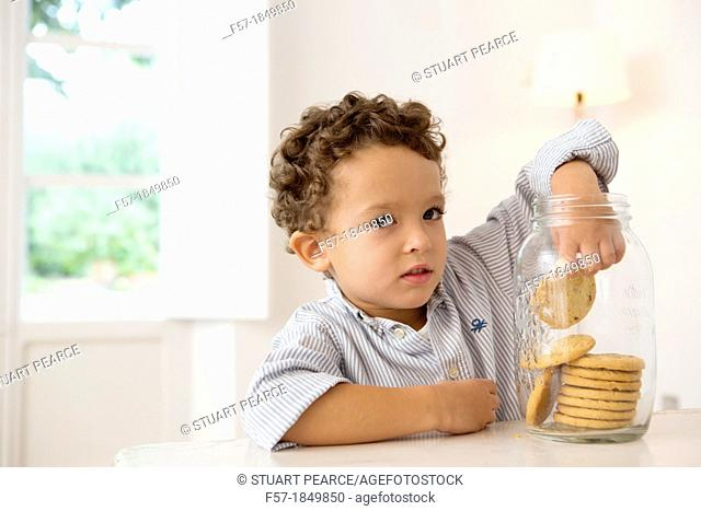 Four year old boy with his hand in the cookie jar