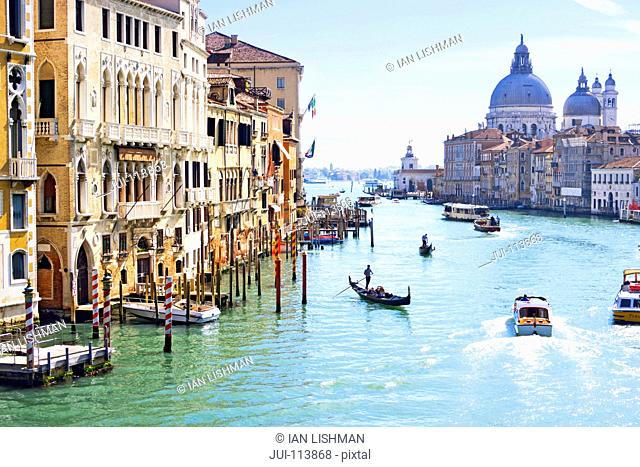 Gondolas and boats in sunny Grand Canal in front of Santa Maria della Salute and architectural buildings in Venice, Italy