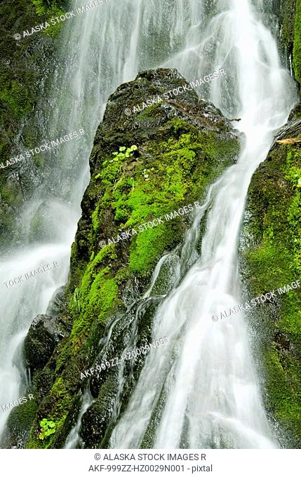 Waterfall flows over green foliage and rock outcrop, Cordova, Southcentral Alaska, Summer