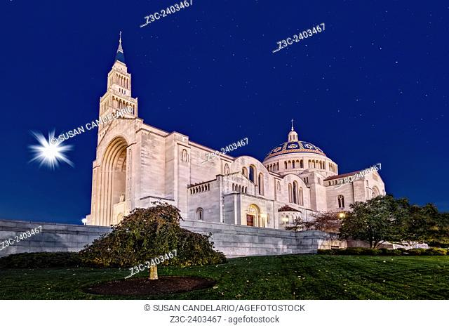 Basilica of the National Shrine of the Immaculate Conception on a clear night with a wanning gibbous setting moon and a starry sky