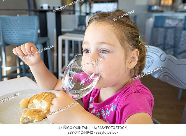 four years old blonde little girl with pink shirt drinking water from cup, sitting indoor in restaurant