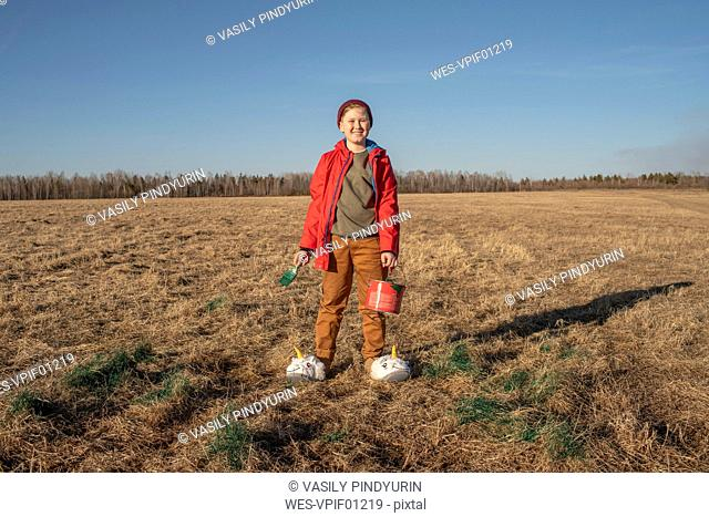 Portrait of smiling boy with paint bucket and brush wearing unicorn slippers in steppe landscape