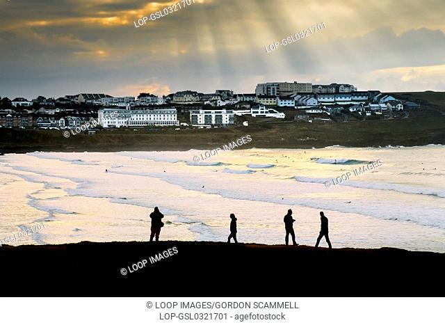 People seen in silhouette as they walk along the coastal path overlooking Fistral Beach