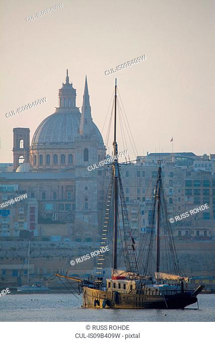 Fishing boat by carmelite church and St Paul's Cathedral, Valletta, Malta
