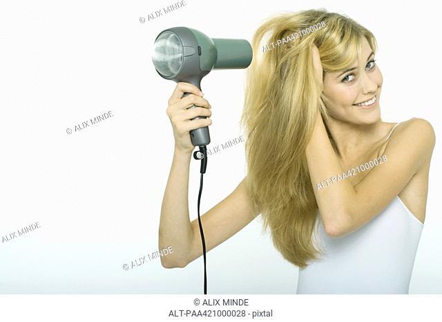 Teenage girl blow-drying hair, smiling at camera