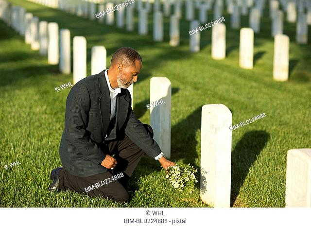 Black man kneeling with bouquet at military cemetery
