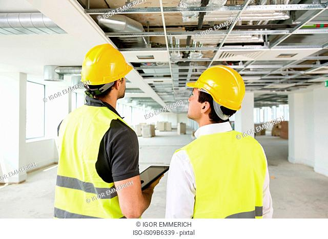 Two men wearing hi vis vest, having discussion in newly constructed office space, rear view