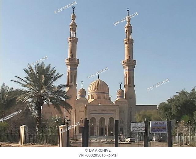 Worshipers enter and exit a beautiful mosque in Baghdad, Iraq