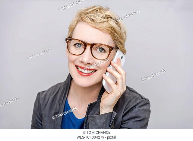 Portrait of smiling blond woman wearing glasses telephoning with smartphone in front of grey background