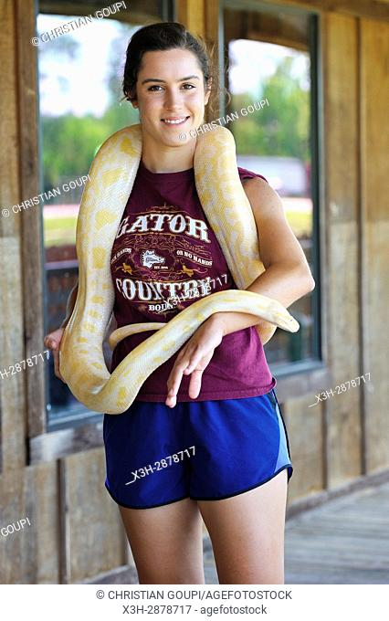 young woman posing with an Albinos Burmese python at Gator Country Wildlife Adventure Park, Beaumont, Texas, United States of America, North America