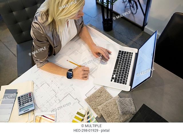 Interior designer with blueprints and swatches working at laptop