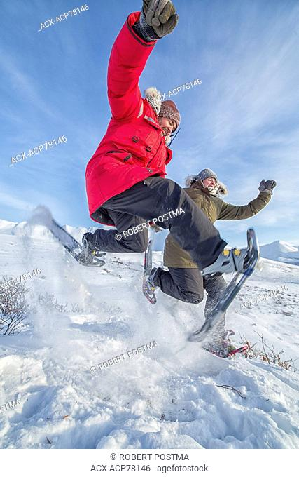 Couple jumping in the snow while wearing snowshoes, northern Yukon