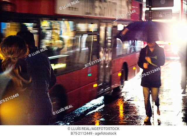 Blur unrecognizable peope with umbrella next to a bus on a rainy day in the city of London, England, UK, Europe