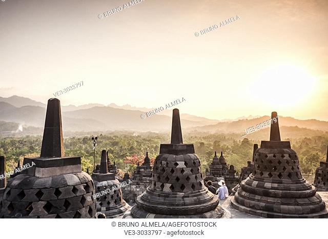 Tourists enjoying sunset over unroofed pyramid of Borobudur Temple, crowned by bell-shaped stone domes (Magelang Regency, Central Java, Indonesia)