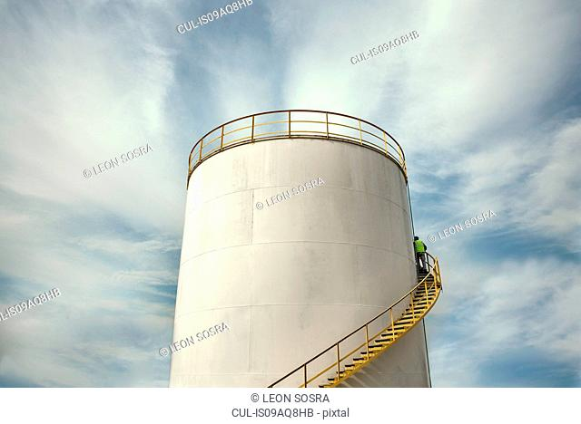 Industrial worker climbing stairs on fuel storage tank