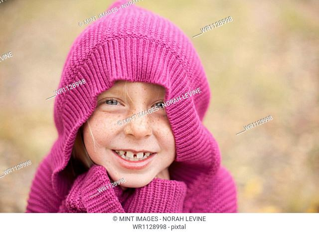 A girl in a magenta hooded sweater, with the hood covering her head, and hands hidden in her cuffs. Keeping warm