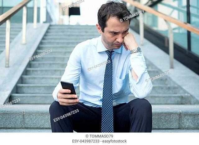 Sad depressed caucasian businessman reading bad news on smartphone
