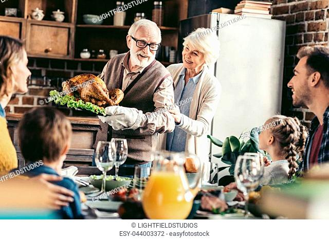grandpa with delicious turkey for thanksgiving dinner with happy family