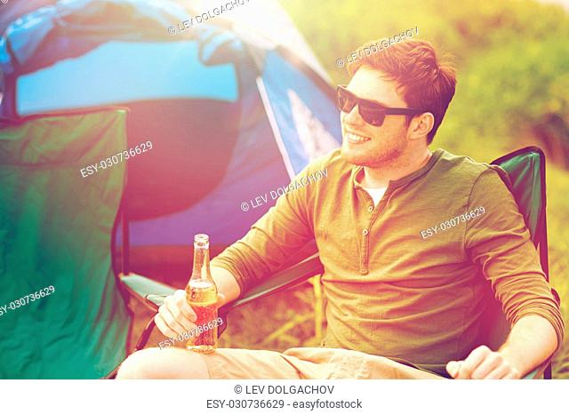 camping, travel, tourism, hike and people concept - happy young man drinking beer at campsite tent