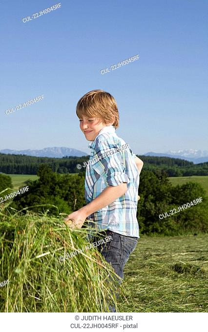 Boy with grass on fork, working