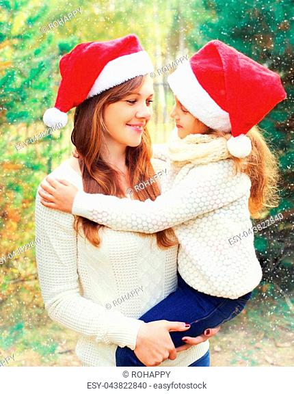 Christmas family, child hugging mother in santa red hats together over a tree having fun