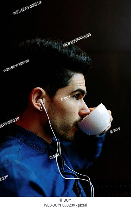 Profile of young man hearing music with earphones while drinking coffee in front of black background