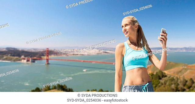 woman with smartphone doing sports over bridge