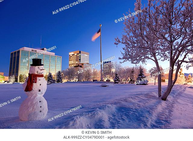 Snowman standing in Delaney Parkstrip with downtown Anchorage in the background at twilight, Southcentral Alaska, Winter. Digitally enhanced
