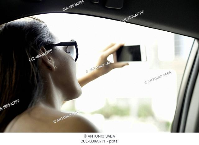 Young woman photographing with smartphone from taxi window