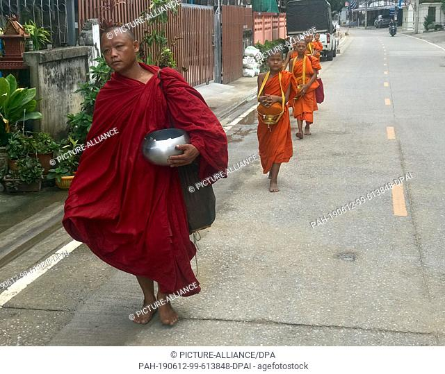 12 June 2019, Thailand, Mae Sai: A Buddhist monk and his novices walk the streets on the border to Myanmar to collect donations