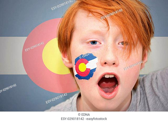 redhead fan boy with colorado state flag painted on his face. on the colorado state flag background