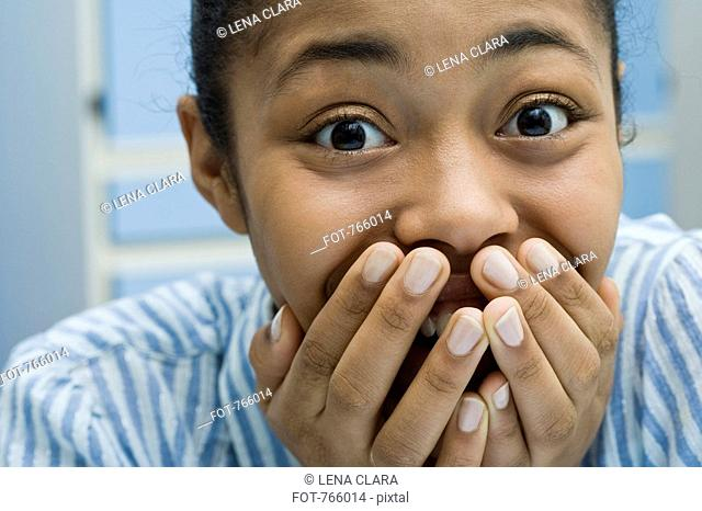 A young woman covering her mouth and laughing