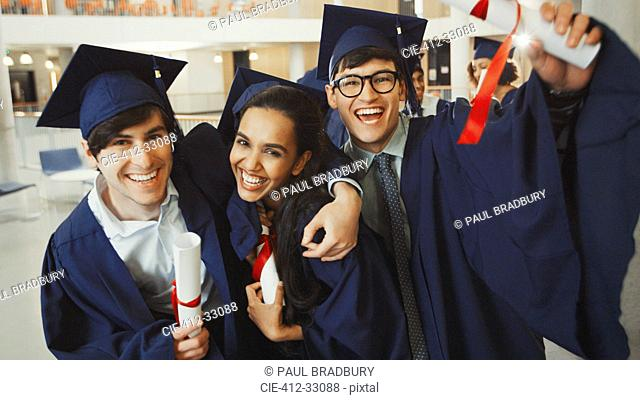 Portrait enthusiastic college graduates in cap and gown with diplomas